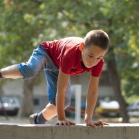 Young boy doing parkour exercise  jumping over wall